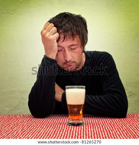 Drunk man at the pub table with a glass of beer.