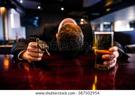 Drunk man holding a beer and car keys in a bar #387502954