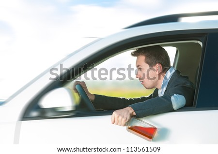 Drunk man holding bottle of whiskey in left hand. Person driving and drinking alcohol. Outdoor action with young guy inside white car. Risky travel. Bright and sunny summer day in background.