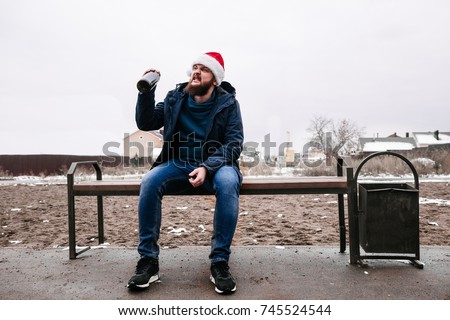 Drunk man in Santa Claus hat sitting on a street bench with a bottle #745524544