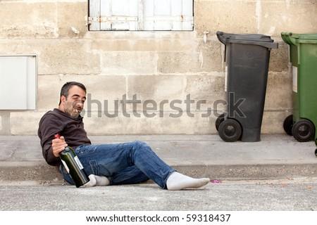 drunk man lying on city street near trashcan