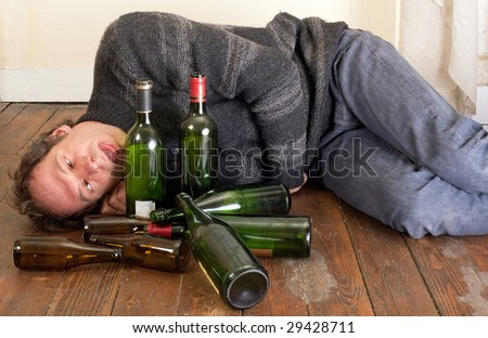drunk man lying on floor with empty bottles