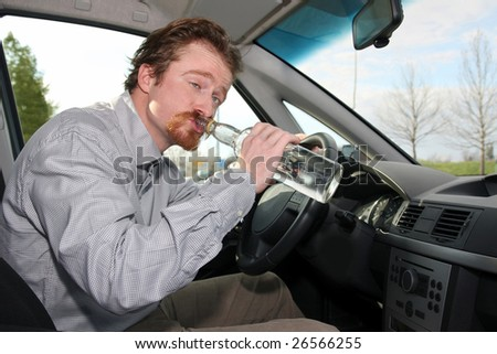 Drunk man sitting in drivers with a bottle alcohol