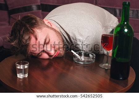 Drunk man sleep on wooden table.