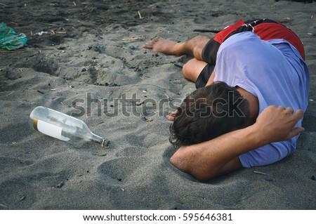 Drunk man sleeping on the sand at the beach #595646381