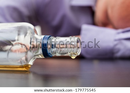 Drunk man sleeping with almost empty bottle of alcohol