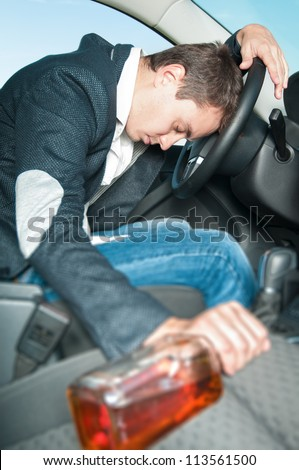 Drunk man sleeps in car with his hand on wheel. Young drunk driver get into accident. Tired person in jeans and gray jacket holding bottle alone in car. Dangerous situation on road.