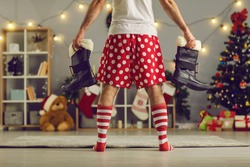 Drunk man who lost his Santa Claus pants comes home in the morning after partying hard all Christmas night wearing red and white striped socks and funny polka dot boxer shorts and holding black boots.