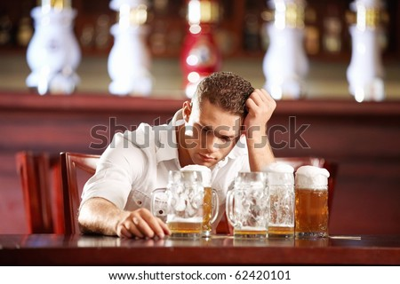 Drunk man with a beer in a pub - stock photo