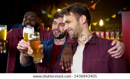 Drunk multiethnic friends clinking beer glasses, spending time in pub, party