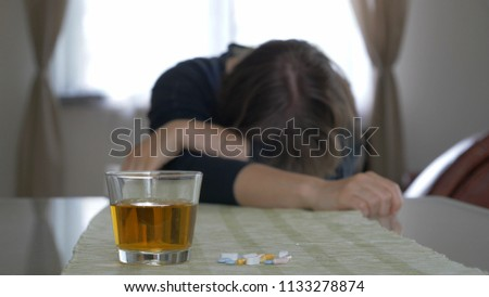 Drunk or sick woman. Acohol and drugs abuse. Woman defocused. Focus on a glass