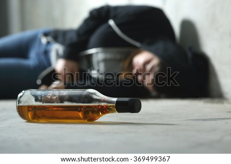 Drunk teenager on the floor in a dark and sad place and an alcohol bottle in the foreground #369499367