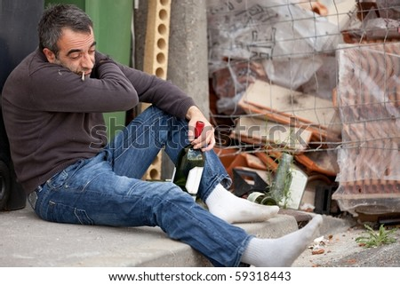 drunk tramp man sitting near trashcan holding bottle of wine