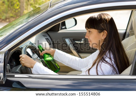 Drunk woman driver smiling as she drives with a bottle of alcohol clutched tightly in one hand, view through the side window