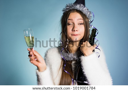drunk woman in a festive cap holding champagne in hands #1019001784