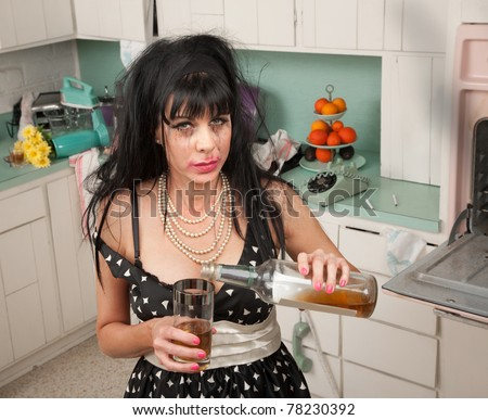 Drunk woman pouring alcohol from a bottle - stock photo