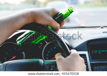 Drunk young man driving a car with a bottle of beer. Don\'t drink and drive concept. Driving under the influence. DUI, Driving while intoxicated. DWI