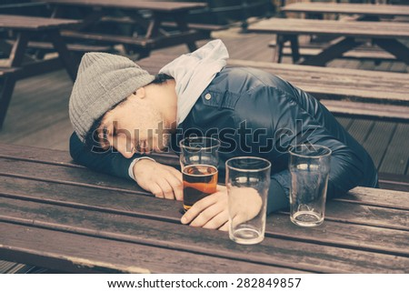 Drunk young man sleeping at pub in London. He is sitting at table outdoor with some empty glasses on the table. #282849857
