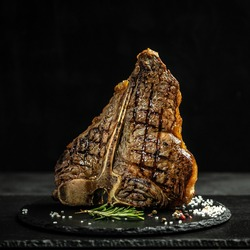 Dry Aged Barbecue Porterhouse Steak T-bone beef steak sliced with large fillet piece with herbs and salt. American meat restaurant. square image,