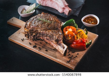 Dry Aged Barbecue Tomahawk Steak, Barbecue Wagyu Tomahawk Steak as top view, Tomahawk steak on wooden cutting board