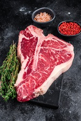 Dry-aged Raw T-bone or porterhouse beef meat Steak with herbs and salt. Black background. Top view.
