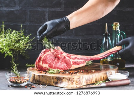 Dry aged raw tomahawk beef steak with ingredients for grilling