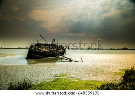 Dry and Wet: this Ship Wreck is patiently waiting for the river tides to pass near Dundalk, Co Louth, in Ireland #648359176