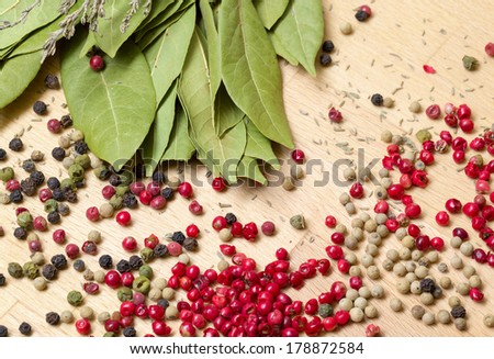Dry bay laurel leaf with multicolored peppercorn closeup on wooden background