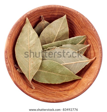 Dry bay leaf in a wooden bowl isolated on white background