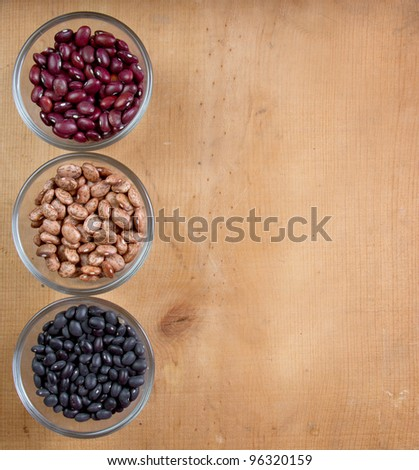 Dry beans in three varieties, black, pinto, kidney, on a wood background