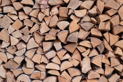 Dry beech wood ready for heating. Wooden logs stacked on top of each other. Stack of wood, firewood, background. Dry chopped firewood logs ready for winter