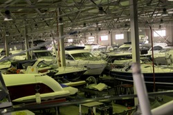 Dry boatyard storage with stack of yachts, indoor shot