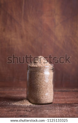 Dry bran in a glass jar on a wooden surface. The product is rich in dietary fiber for digestion #1125133325