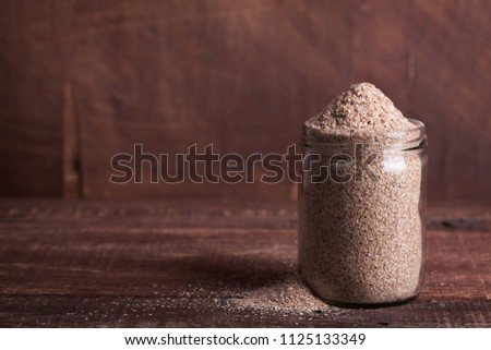 Dry bran in a glass jar on a wooden surface. The product is rich in dietary fiber for digestion #1125133349
