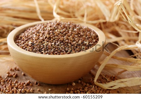 Dry buckwheat groats on wooden bowl