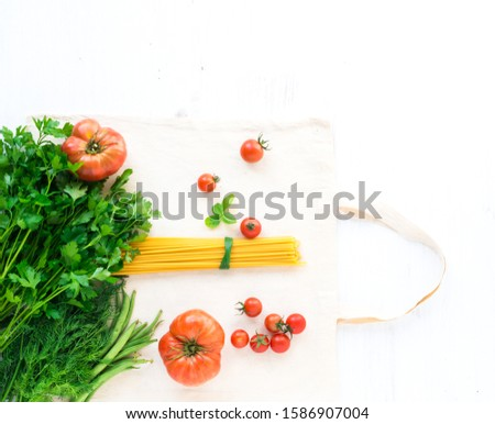 Dry bunches of pasta for cooking traditional Italian pastas with herbs and tomatoes on a shopping bag after the supermarket. View from above
