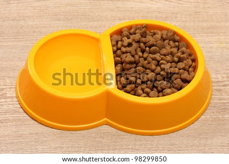 dry cat food and water in yellow bowl on wooden background