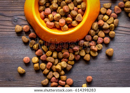 dry cat food in bowl on wooden background top view #614398283