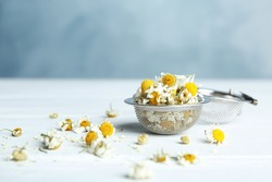 Dry chamomile flowers in infuser on white wooden table