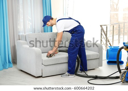 Dry cleaner's employee removing dirt from furniture in flat