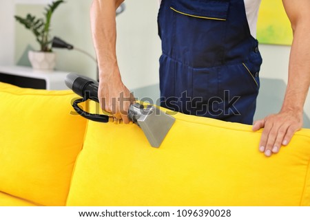Dry cleaning worker removing dirt from sofa indoors - Shutterstock ID 1096390028