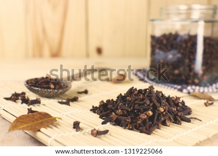 Dry clove and dry clove spoon with dry clove bottle on wooden background.jpg #1319225066