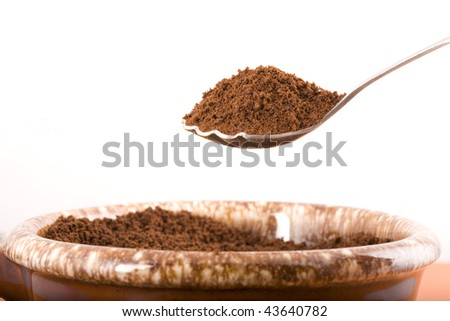 Dry coffee grounds heaped on a spoon against a white background.