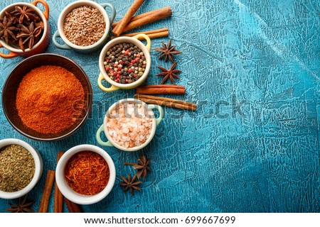 Shutterstock Dry colorful spices and condiments anise, paprika, saffron, pepper, salt, bay leaf, cinnamon in small bowls on blue background. Top view