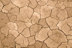 Dry cracked earth as a background close-up. Environmental disaster. Drought.