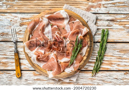 Dry cured parma ham or Prosciutto crudo on a wooden board with rosemary. White wooden background. Top View Foto stock ©