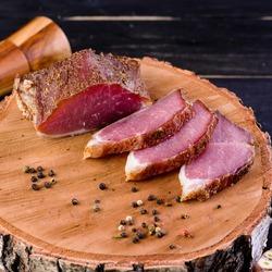 dry-cured pork fillet Dried pork, polendwitz, jerky tenderloin on wooden background. Cured pork meat. Polenitsa is a dry-cured filet. Dish of Belarusian cuisine