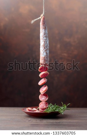 Dry-cured sausage with rosemary on a old wooden table.