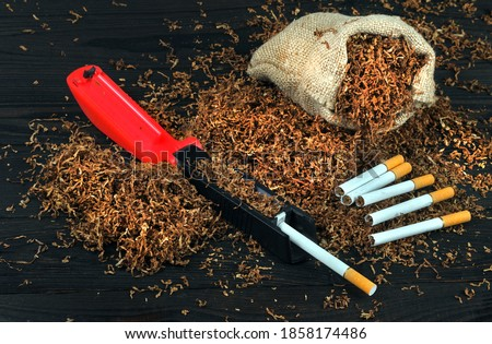 dry cut tobacco leaf, cigarettes and cigarette machine on wooden table. handmade cigarettes