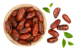 dry dates with green leaves in wooden bowl isolated on white background. Top view. Flat lay pattern
